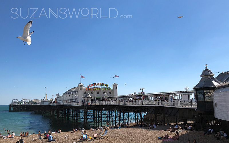 The Brighton Palace Pier on a bright sunny day with people on the beach in front